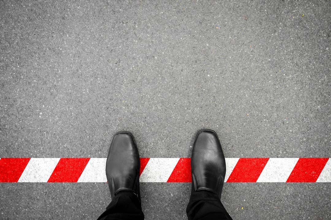 black shoes stepping on a red and white line