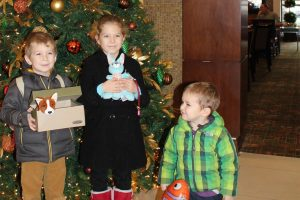 Emily kids holding presents in front of a Christmas tree
