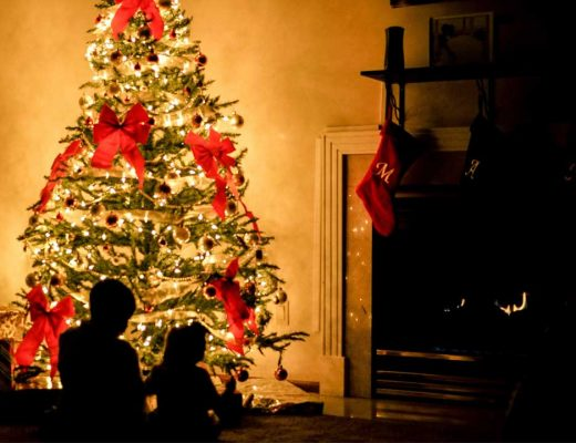 Kids sitting by Christmas Tree