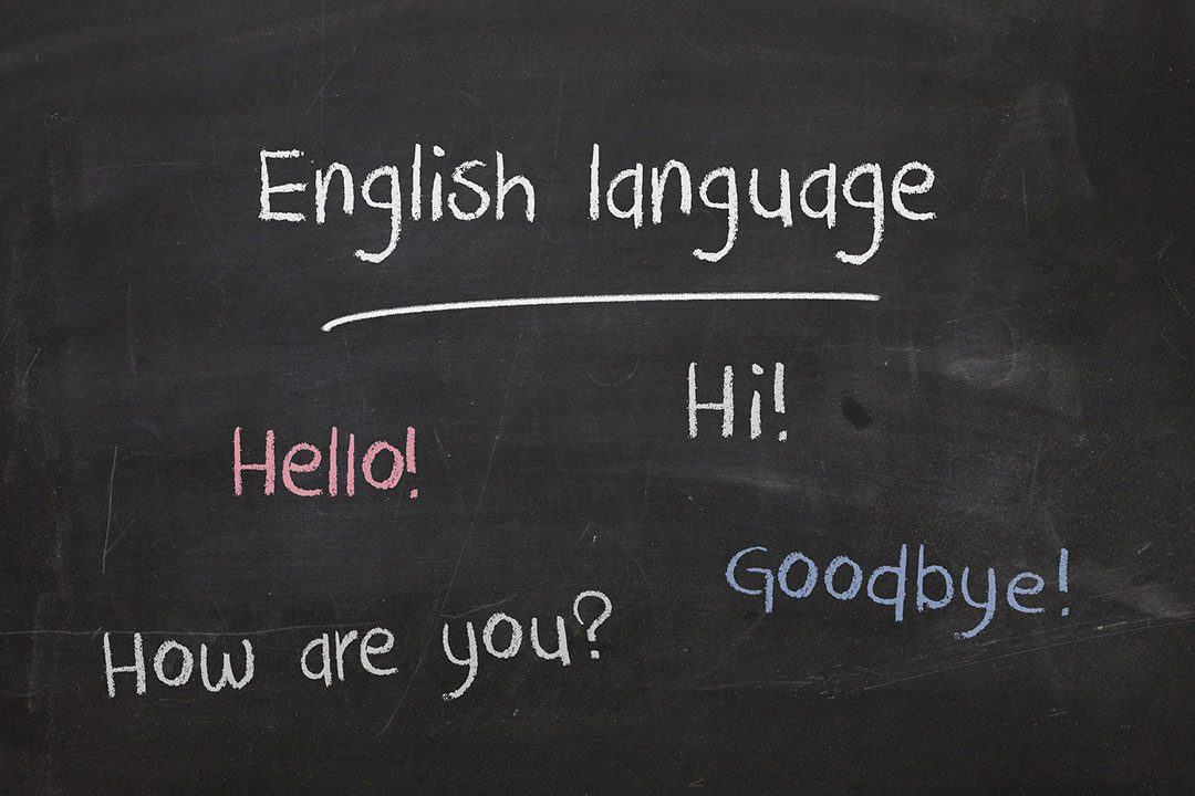 English language written on black board in chalk with words hello, hi, how are you, and goodby.