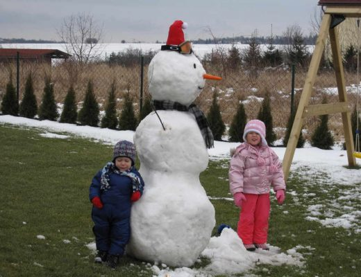 Anna & Oliver beside a large snowman in our yard