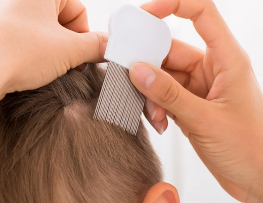 Treatment of head lice on boy's hair with comb
