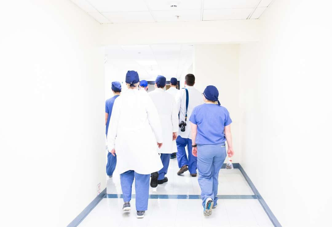 the backs of doctors walking down a hospital corridor