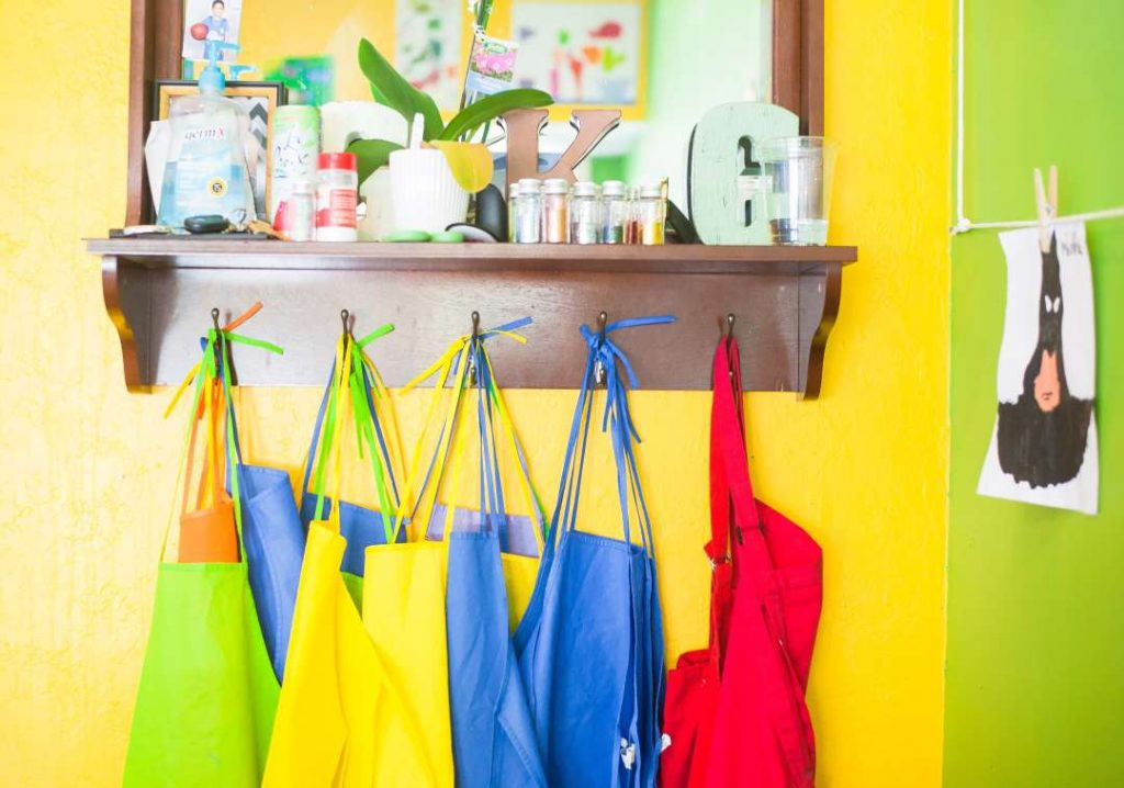 brightly colored painting smocks hanging on pegs