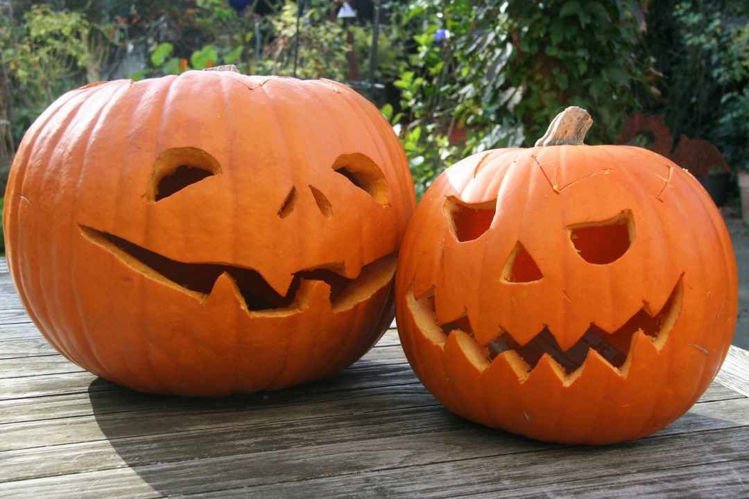 two carved jack-o-lanterns on a table