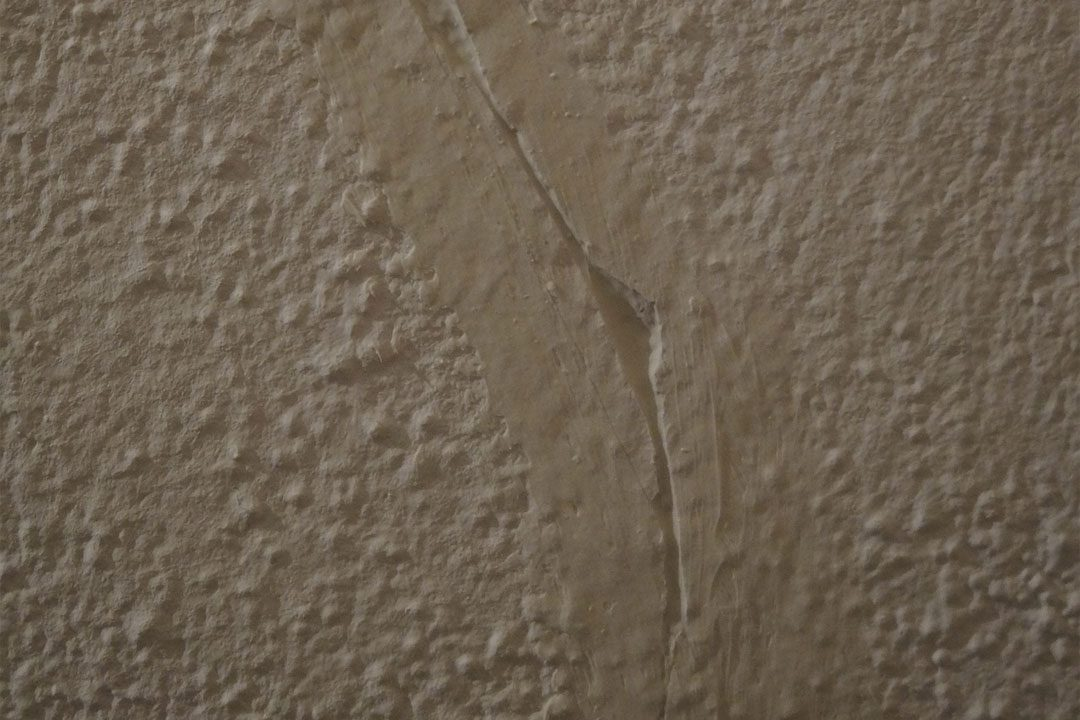Crack in wall covered over by coat of paint