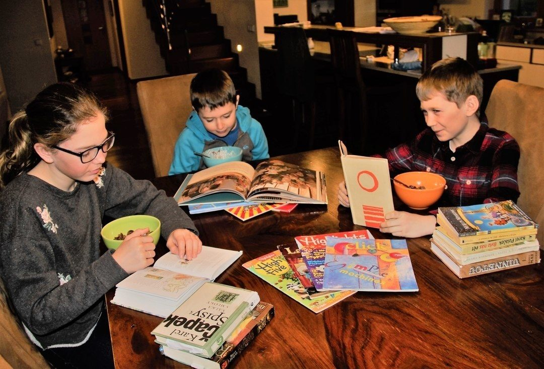 Anna, Oliver & Sam at the kitchen table reading with books and magazines around them