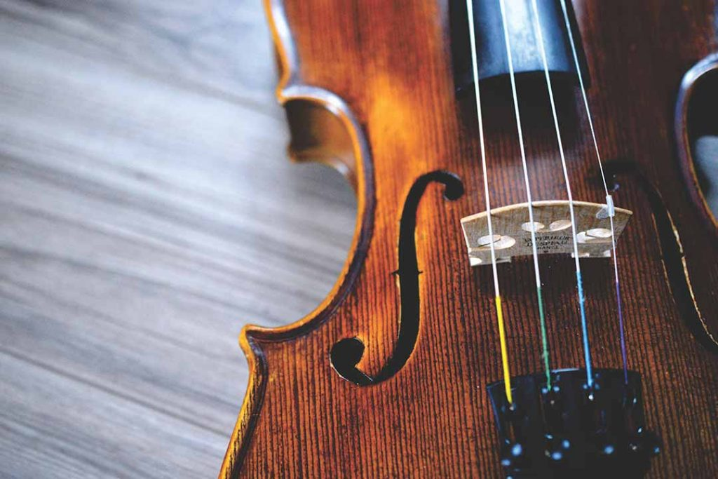 Violin strings in close-up photo by Providence Doucet (@providence) on Unsplash