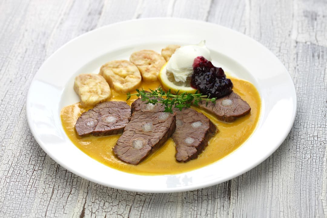 svickova na smetane (beef in sour cream sauce) served with knedlik (bread dumpling), traditional Czech cuisine - photo by bonchan/Shutterstock.com
