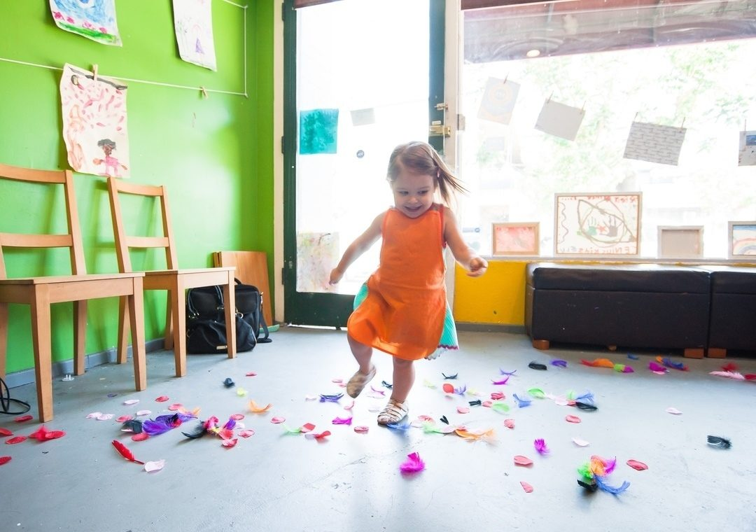 toddler running through coloured paper in a mother's centre