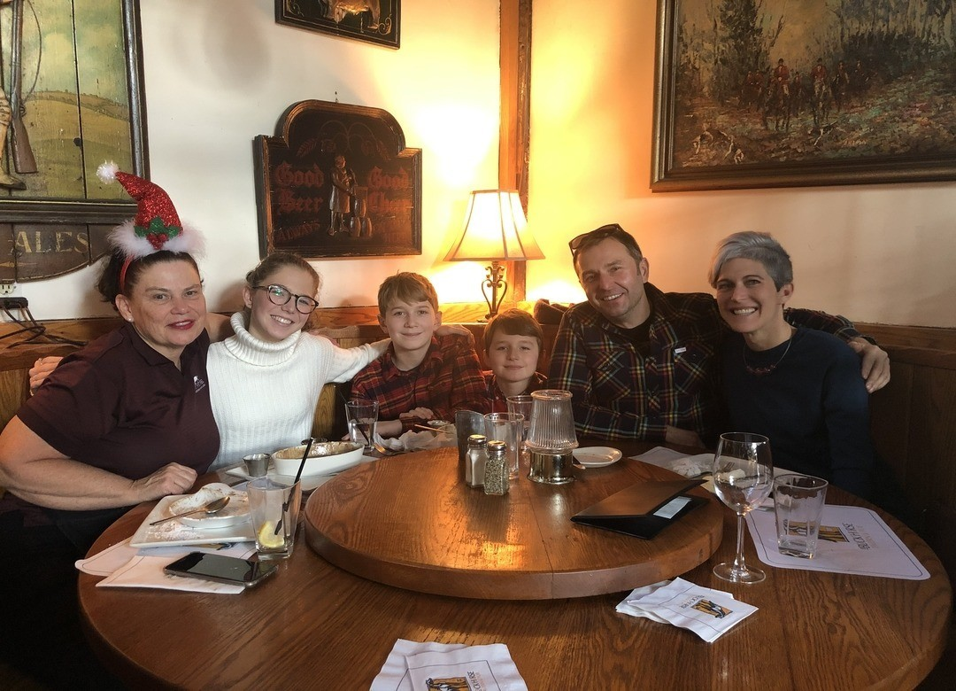 Our family sitting with Kathleen at a table